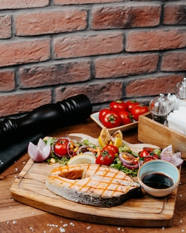 Het zijaanzicht van geroosterde zalm diende met de saus van verse groentencitroen op houten raad