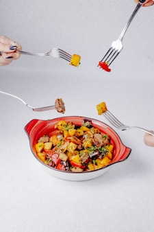 Het zijaanzicht van handen houdt vorken over de kom met gestoofde vleesaardappels en groenten