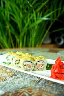 Het zijaanzicht van het traditionele japanse broodje van keukensushi met tonijn diende met gember op groen
