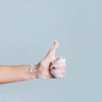 Het zijaanzicht van het zeepachtige hand geven beduimelt omhoog