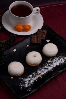 Het zijaanzicht van koekjes met kokosnotenvlokken en chocolade op een zwarte raad diende met thee