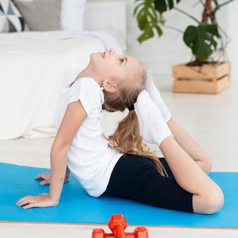 Het zijaanzicht van meisje het praktizeren yoga stelt thuis