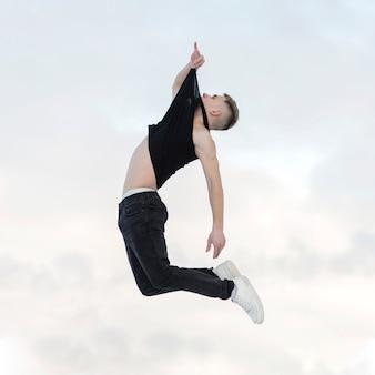 Het zijaanzicht van mid-air stelt door hiphopdanser