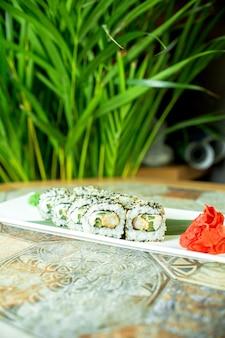 Het zijaanzicht van sushi stelt broodjes met de roomkaas van het krabvlees en avocado in kaviaar van vliegende vissen die met gemberplakken op groen worden geserveerd