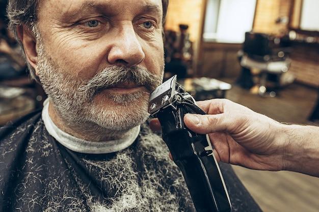 Het zijaanzichtportret van de close-up van de knappe hogere gebaarde kaukasische mens die baard het verzorgen in moderne herenkapper krijgt.