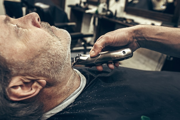Het zijaanzichtportret van het close-up zijprofiel van knappe hogere gebaarde kaukasische mens die baard het verzorgen in moderne herenkapper krijgen.