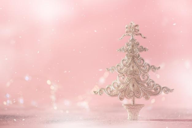 Het zilver schittert kerstboom op roze achtergrond met lichten bokeh, exemplaarruimte.