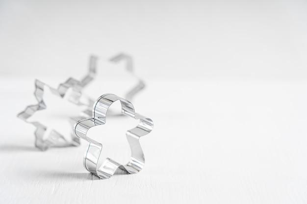 Het zilveren keukengerei van de staalkoekjessnijders in vorm van peperkoekman op witte houten lijst