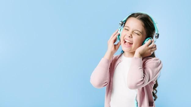 Het zingen van het meisje in hoofdtelefoons in studio