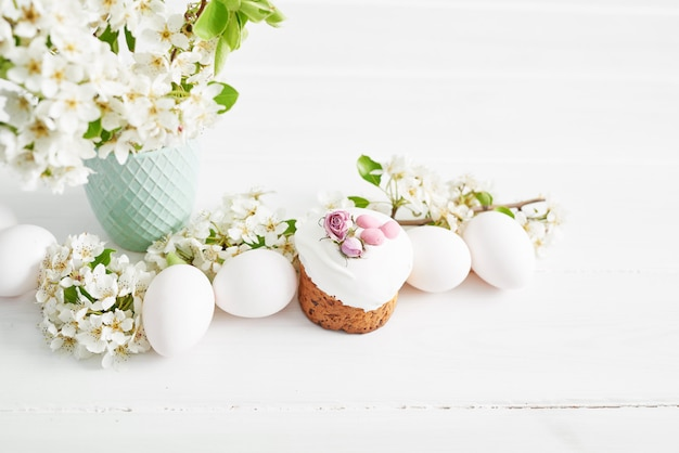 Het zoete brood van pasen, pasen-cake met bloemen en peperkoek. vakantie ontbijt concept met kopie ruimte. pasen wenskaartsjabloon. zelfgemaakte pasques. pasen-snoepjes op witte lijst.