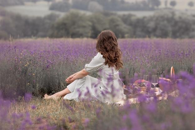 Het zomerseizoen. lavendelvelden. een meisje met een mand met lavendelveld. kijkend in de verte, een foto van achteren.
