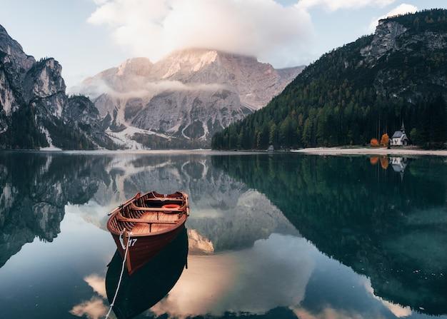 Het zonlicht op de top. houten boot op het kristalmeer met majestueuze erachter berg. reflectie in het water. kapel ligt aan de rechter kust