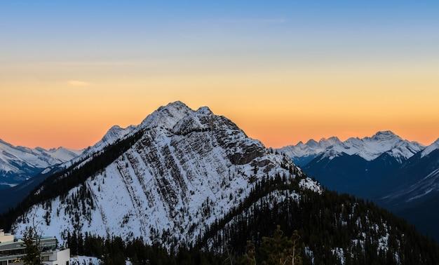 Het zonsonderganglandschap van sneeuw dekte canadese rotsachtige bergen bij het nationale park van banff in alberta, canada af