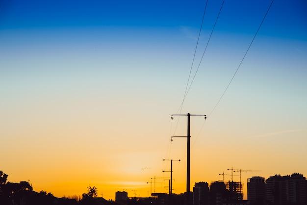 Het zonsondergangsilhouet van elektrische torens op een gebied in aanbouw, kopieert ruimte.