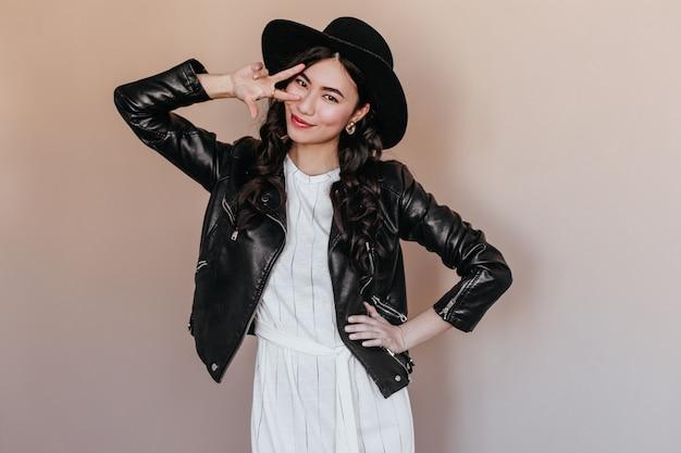 Het zorgeloze aziatische vrouw stellen met vredesteken. studio shot van gelukkig koreaanse vrouw draagt stijlvolle hoed en leren jas.