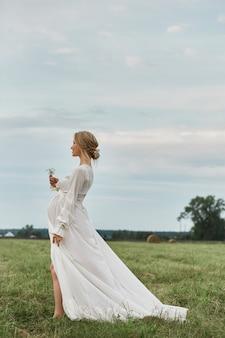 Het zwangere meisje loopt op een gebied dichtbij hooibergen in een lange witte kleding