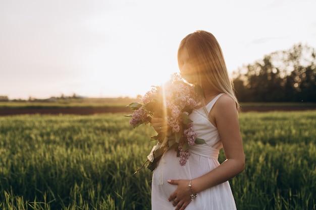 Het zwangere meisje staat op het veevoer