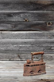 Het zware en roestige oude kolenijzer ligt op een houten oppervlak