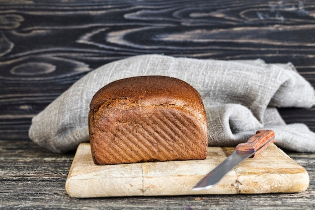Het zwarte bittere brood van de roggemeel, close-up van voedsel op keuken scherpe raad