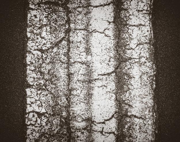 Het zwarte detail van de asfalttextuur met witte lijn