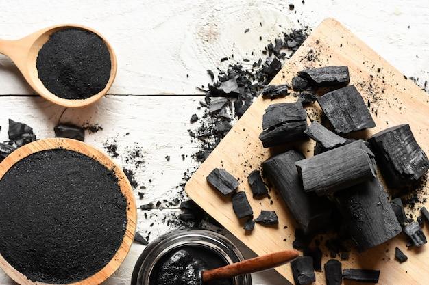 Het zwarte houtskoolpoeder voor gezichtsmasker en schrobt, geplaatst op een wit houten lijst, gezondheids en schoonheidsconcept.