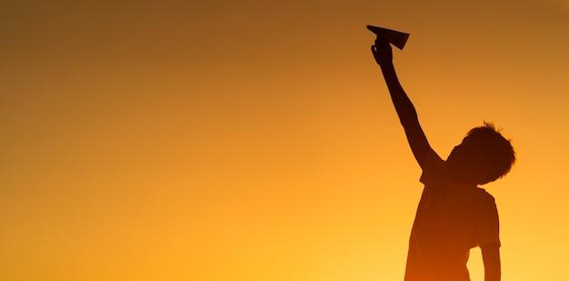 Het zwarte silhouet dat van de jongen zich tegen de oranje achtergrond van de de zomerzonsondergang bevindt