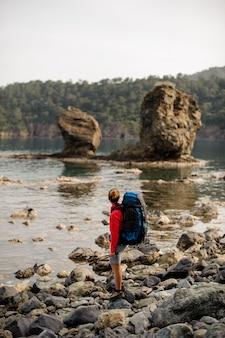 Het zwervermeisje bekijkt tweelingrotsen bij kust