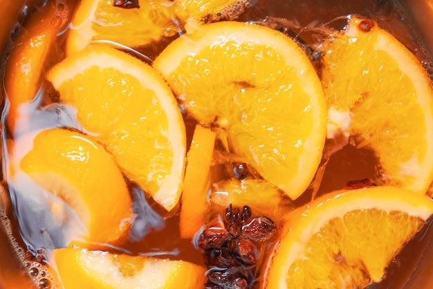 Hete alcoholische glühwein maken met sinaasappels en kruiden. kerstdranken koken in de metalen pan. glintwijn van rozenwijn met citrus, kruidnagel, steranijs, kaneel.