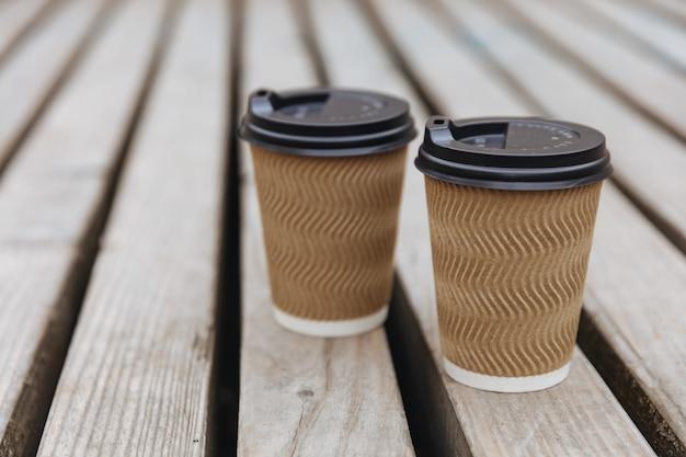Hete aroma koffie in geribbelde papieren bekers met zwarte deksels