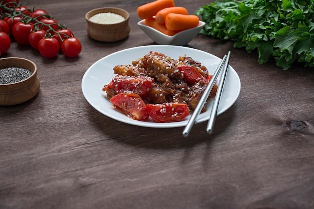 Hete aubergine en tomatensalade in koreaanse stijl met sesamzaadjes en kruiden. aziatisch eten. vegetarisch gerecht. hout achtergrond