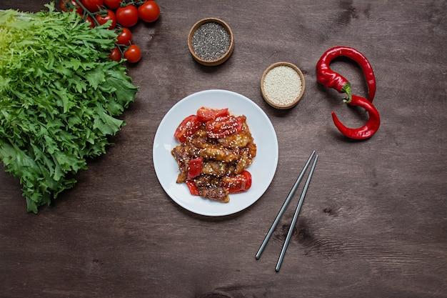 Hete aubergine en tomatensalade in koreaanse stijl met sesamzaadjes en kruiden. aziatisch eten. vegetarisch gerecht. hout