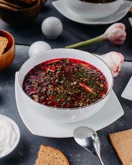 Hete borsh soep met gekookte groenten in ronde witte plaat samen met brood loafs eieren op grijze tafel