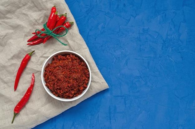 Hete chilipepersaus harissa, traditionele tunesië, marokkaanse, arabische keuken adjika, chili specerijen en verse rode chili pepers, op blauwe achtergrond.