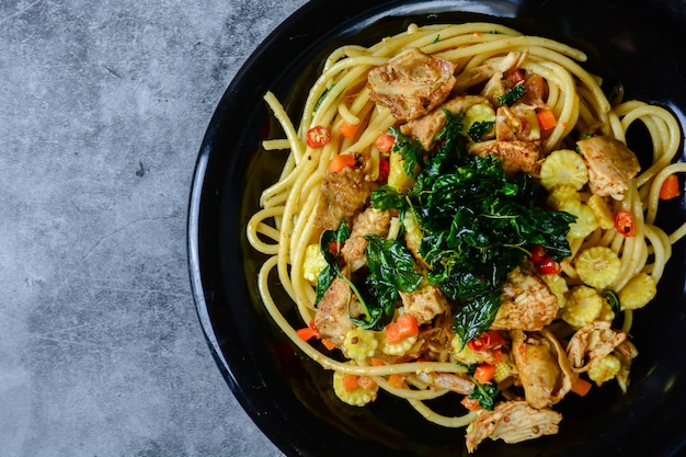 Hete en kruidige kippenspaghetti, topping met knapperige zoete basilicum en gesneden babymaïs