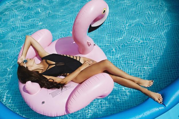Hete en modieuze brunette, fitnessmodel meisje met perfect sexy lichaam in stijlvolle zwarte bikini en glamoureuze zonnebril, bruinen op een opblaasbare roze flamingo en poseren bij het zwembad