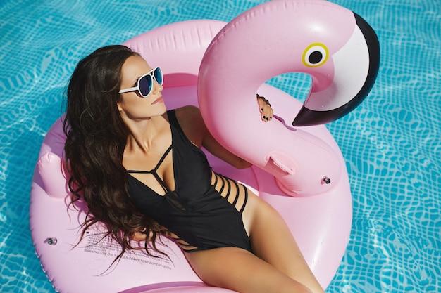 Hete en modieuze brunette model vrouw met perfect sexy lichaam in stijlvolle zwarte bikini en glamoureuze zonnebril, zit op de zwevende roze flamingo en poseert bij het zwembad