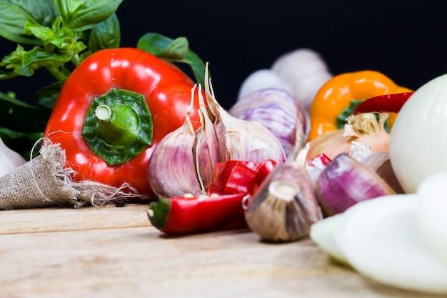 Hete en zoete paprika knoflook en andere groenten en kruiden op de snijplank tijdens het koken keukentafel tijdens het koken van voedsel close-up