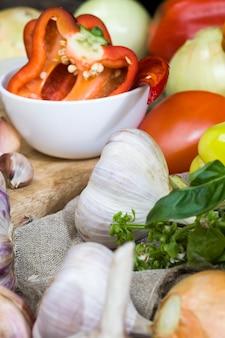 Hete en zoete rode paprika knoflook en andere groenten en kruiden op de snijplank tijdens het koken keukentafel tijdens het koken van voedsel