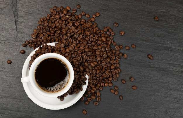 Hete espresso-kopje en koffiebonen op zwarte stenen achtergrond bovenaanzicht.