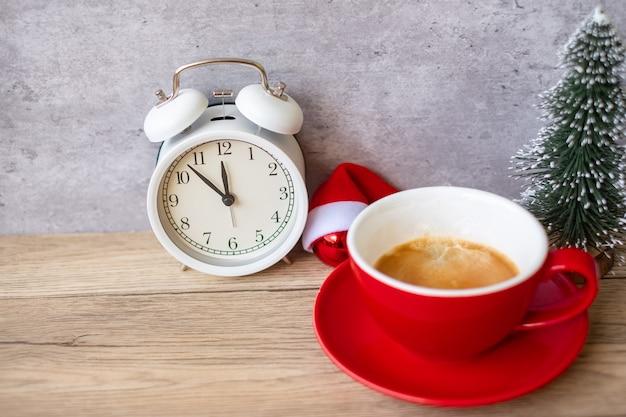 Hete espressokoffie en vintage klok op tafel, rode koffiekop in café of thuis in de ochtend. activiteit, dagelijkse routine, ochtend, training en werk-privébalansconcept