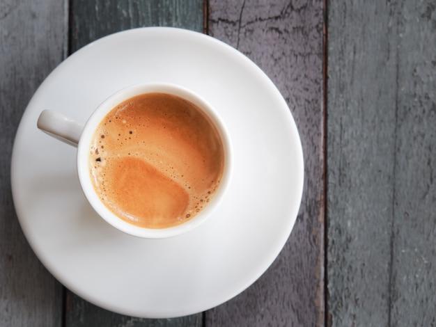 Hete espressokop op houten lijst.