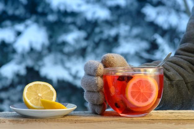 Hete fruitthee met citroenringen op een de winterdag. een gebreide gehandschoende hand houdt de glazen mok vast.