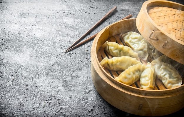 Hete gedza-dumplings in een bamboestoomboot. op zwarte rustieke achtergrond