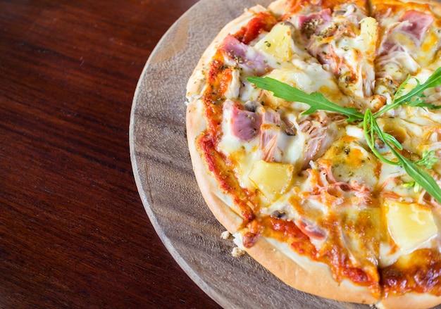 Hete gesneden hawaiiaanse pizza op een houten bord.