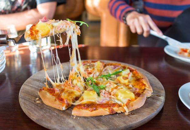 Hete gesneden hawaiiaanse pizza op een houten raad en de mensenhand die plakken van pizza nemen.