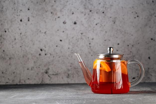 Hete gezonde zwarte thee met citroen in glazen theepot