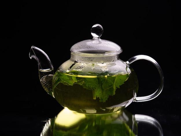 Hete glazen theepot op een zwarte achtergrond, groene muntthee, kruidenthee en gezond drankje concept