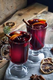 Hete glühwein in twee glazen met fruit en kruiden op houten tafel
