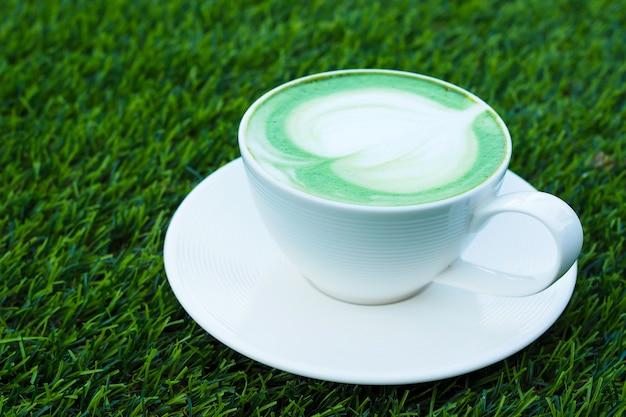 Hete groene theematcha latte in witte kop op groene grasachtergrond