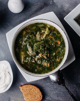 Hete groentesoep met groenen gekookte groenten binnen ronde witte plaat samen met brood loafs eieren op grijze tafel